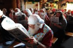 Student Santas hide their faces with a newspaper from the visiting children as not to confuse them while a dressed up Santa is performing during the Charles W. Howard Santa Claus School workshop on October 17, 2008 in Midland, Michigan.
