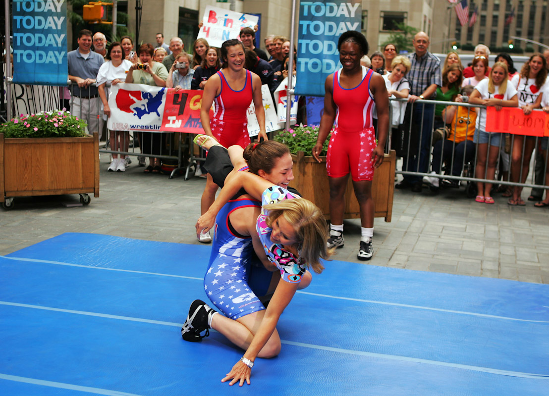 Sara McMann of the US Olympic Woman's Wrestling team flips Katie Couric of the Today Show as Tela O'Donnell and Toccara Montgomery look on June 22, 2004 in Staten Island, New York.