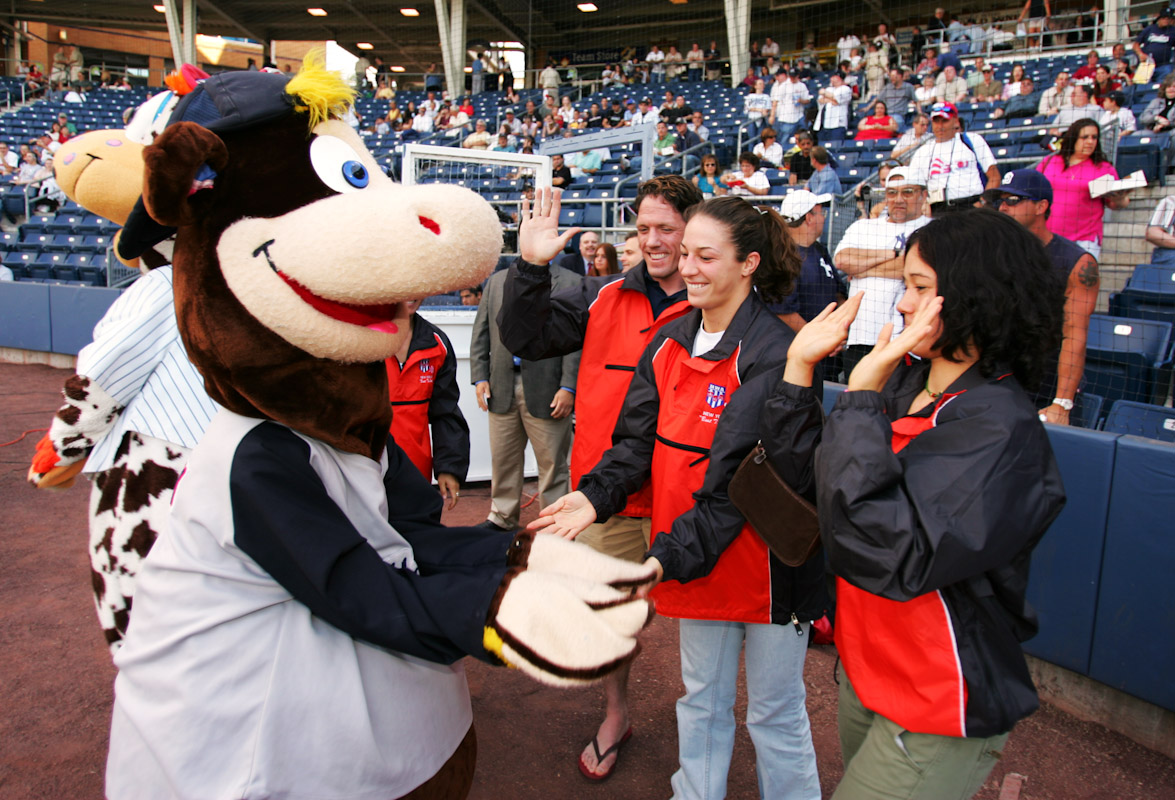 Tela O'Donnell, Sara McMann, and and Head Coach Terry Steiner of the US Olympic Woman's Wrestling team greet Staten Island Yankees team mascot at their home opener on June 22, 2004 in Staten Island, New York.