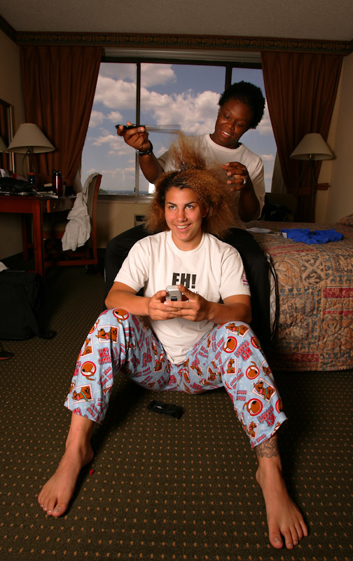 Toccara Montgomery of the US Olympic Woman's Wrestling team braids the hair of training partner Stephany Lee in her room at the Staten Island Hotel between sessions at their training camp at Monsignor Farrell High School on June 27, 2004 in Staten Island, New York.