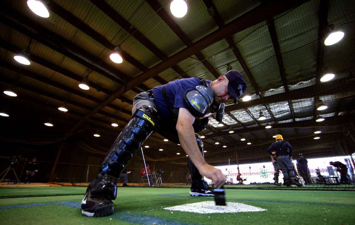 A student umpire wipes off home plate before calling balls and strikes in a simulated game while under the watch of an instructor who is playing the role of a team manager at the indoor batting cages during the Jim Evans Academy of Professional Umpiring on January 28, 2011 at the Houston Astros Spring Training Complex  in Kissimmee, Florida.