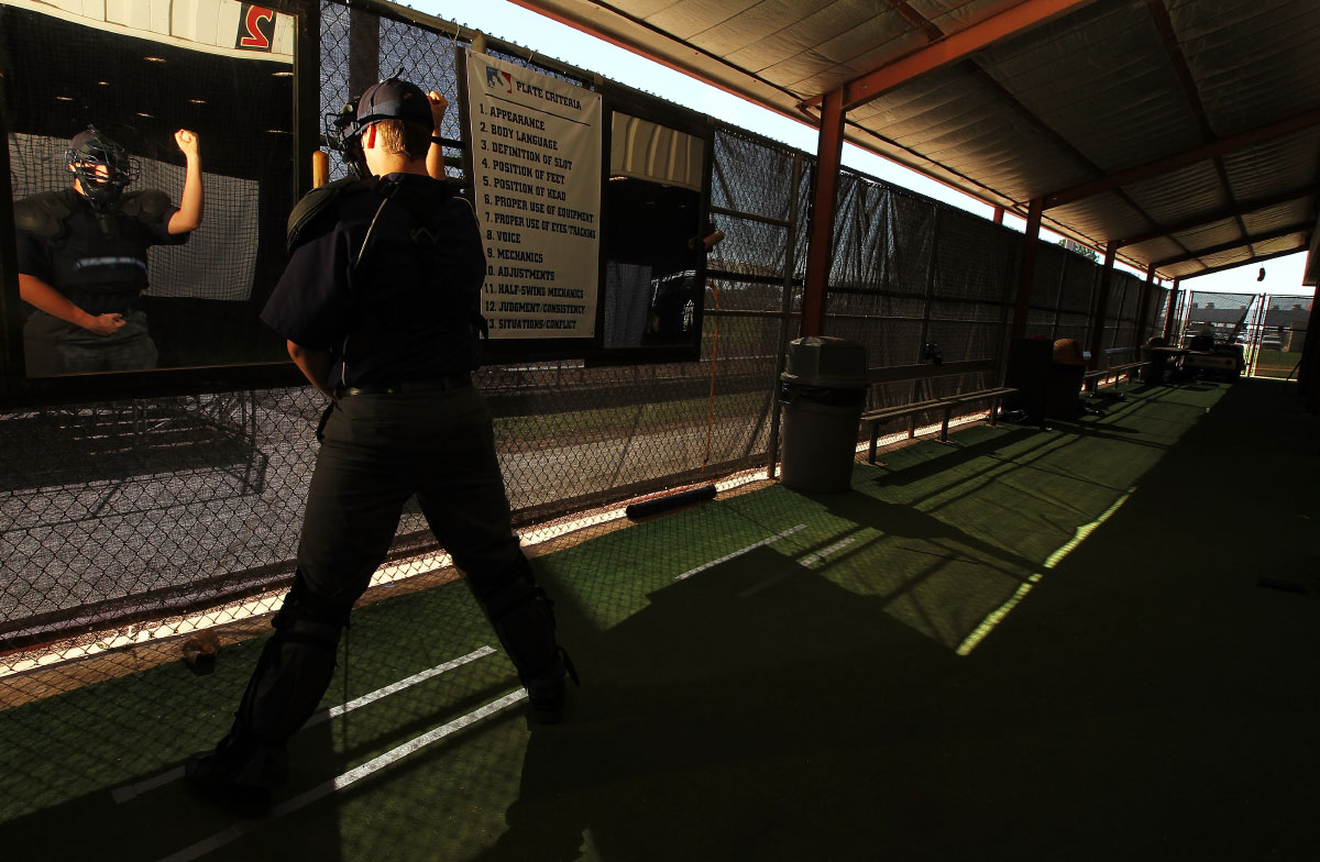 A student umpire works on his hand motion in the mirror before calling balls and strikes in a simulated game while under the watch of an instructor who is playing the role of a team manager at the indoor batting cages during the Jim Evans Academy of Professional Umpiring on January 27, 2011 at the Houston Astros Spring Training Complex  in Kissimmee, Florida.