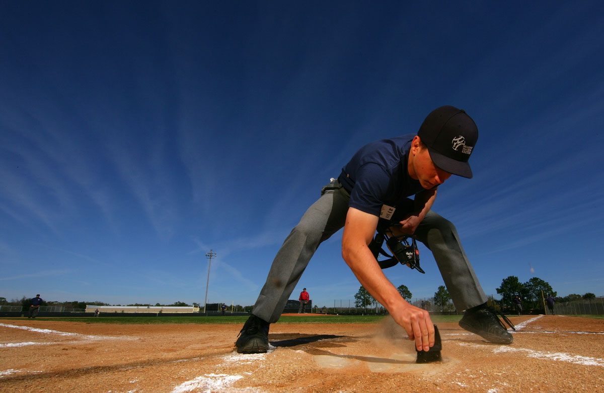A student Umpire cleans home plate before participationg  in a simulated baseball game during the Jim Evans Academy of Professional Umpiring on January 27, 2011 at the Houston Astros Spring Training Complex  in Kissimmee, Florida.