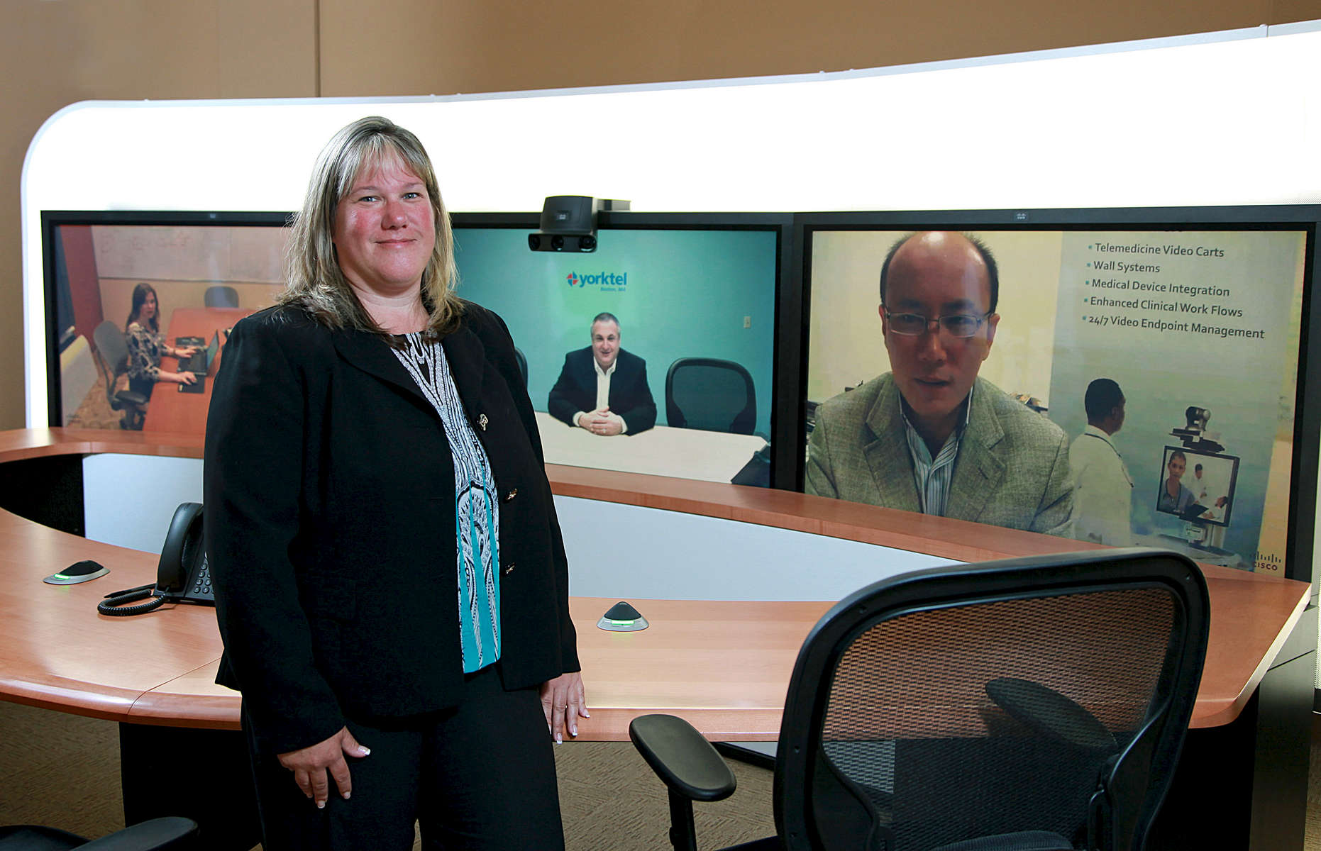 Judi Pulig, CFO of Yorktel, an Eatontown, New Jersey based Video Conferencing Company, in one of their Corporate Video Conferencing Rooms.  On the screens (L to R) are Amyanne Barone, Account Manager; Eric Richman, VP Corporate Services in Boston, MA and Bin Guan, Chief Technology Officer.  CREDIT: Bill Denver for the Wall Street JournalCFOSKILLS