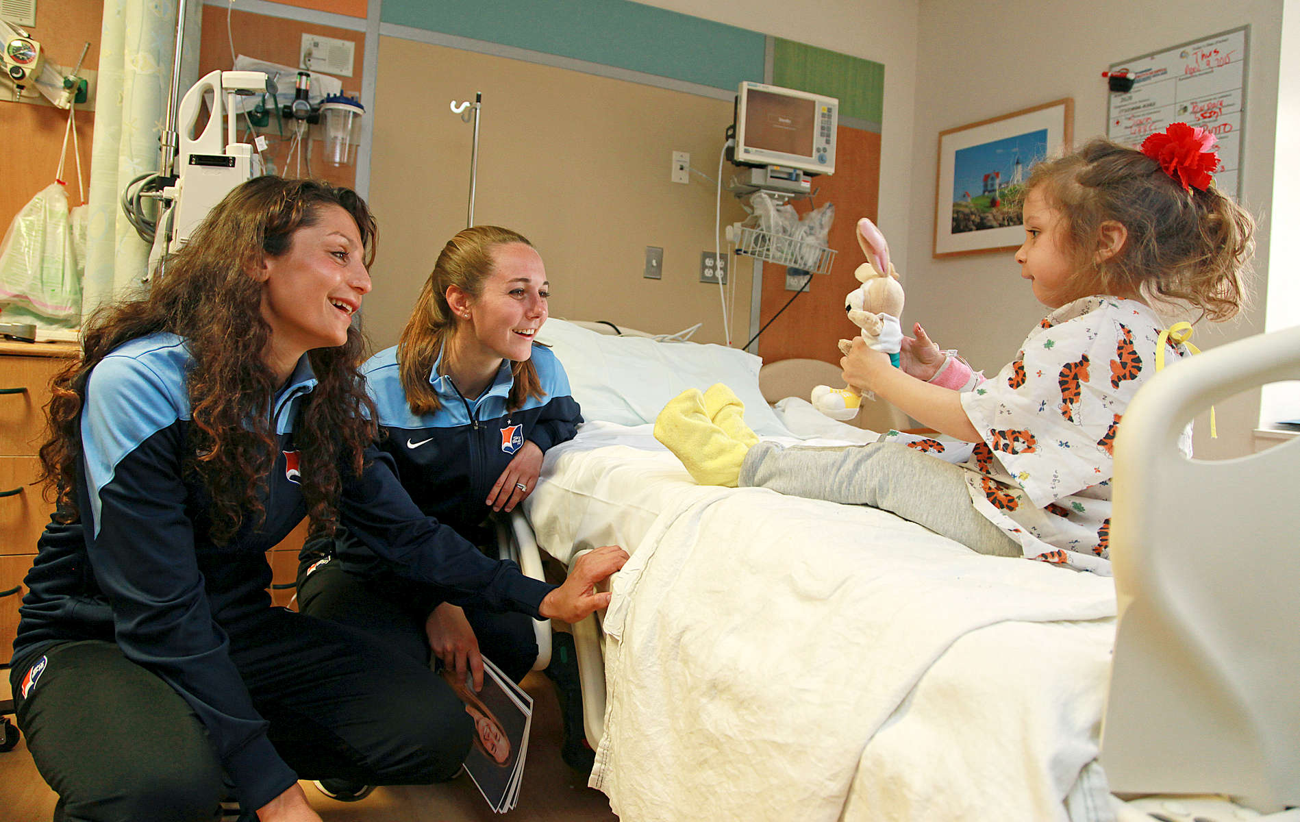 Professional Women's Soccer Player Nadia Nadim (L) , who was born in Kabul, Afghanistan visits 3 year old Valentina, with teammate and roommate Katy Freels,  at Jersey Shore Medical Center in Neptune, NJ.