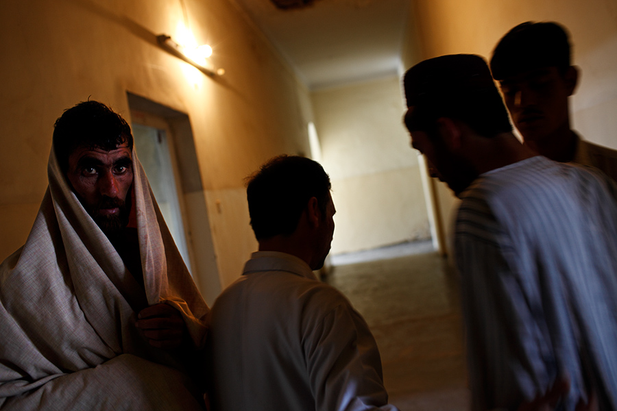 Patients stand in the hallway of the drug dependency ward at the Psychiatric & Drug Dependency Treatment Hospital in Kabul, Afghanistan.  This hospital is the sole government-run hospital of its kind, equipped with only 60 beds.  Twenty beds each for men's and women's psychiatric wards, but the remaining 20 beds for the drug dependency ward are only for the male patients.