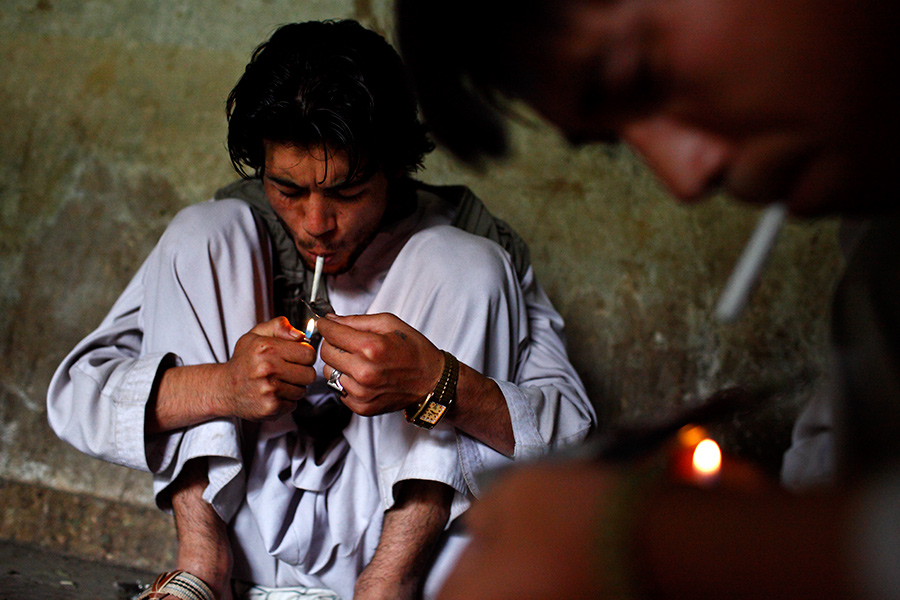 Men smoke heroin at the destroyed Russian Cultural Center, a well-known place for drug activities in Kabul, Afghanistan.  Experts state that heroin is easily obtainable along with other drugs, such as hashish and opium.  One gram of heroin goes for about 200 to 250 Afghani, which is about US$4.00 to 5.00.
