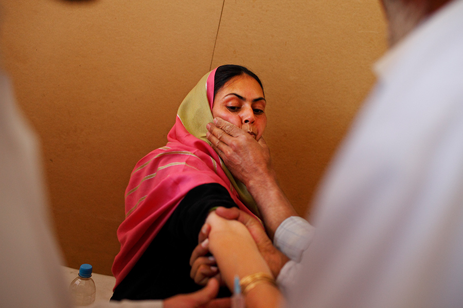 A husband tries to control and calm his wife by holding her face while she receives a shot at the outpatient department.  A medical staff stated that the hospital only possesses about 30 to 40% of ideal medicine for its inpatients, and 10% for its outpatients.