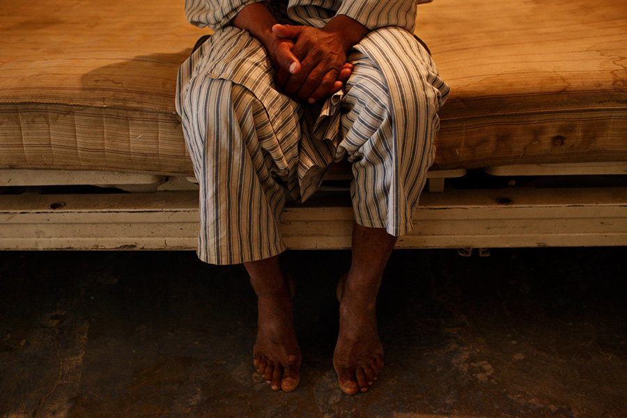 A male psychiatric patient sits quietly on a bed in the hallway of the men's psychiatric ward.  According to a medical staff, the patients are supposed to bring their own sandals, spoon, teacup and such, but some can't even afford to bring these basic items.  Some walk the concrete hallways and the lavatories barefoot.