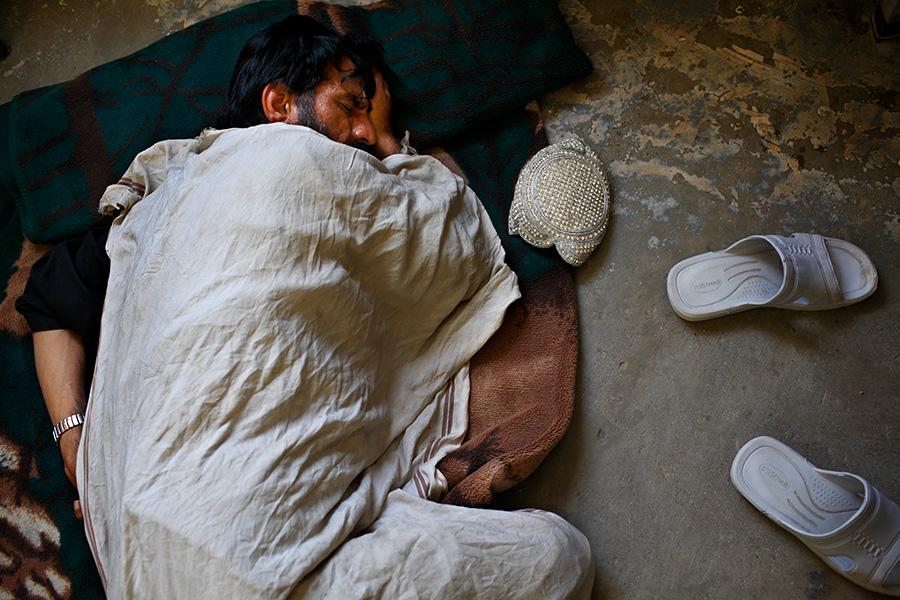 A man sleeps on the floor of the men's psychiatric ward.