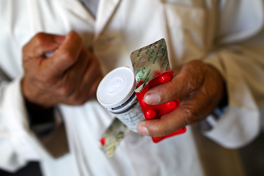 A medical staff gives out medicine after a meal.  The hospital currently possesses only 1 kind of antidepressant and 2 kinds of antipsychotic medicines, which were donated by foreign countries.