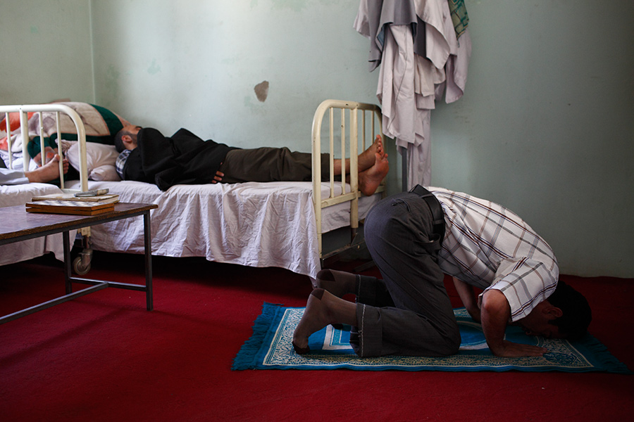 A medical staff prays while other staff members take a rest inside the doctor's office.  The medical staff's monthly income is 8400 Afghani, about US$168.00.  Being the sole government run hospital of its kind, patients come from everywhere nonstop, making it very busy.