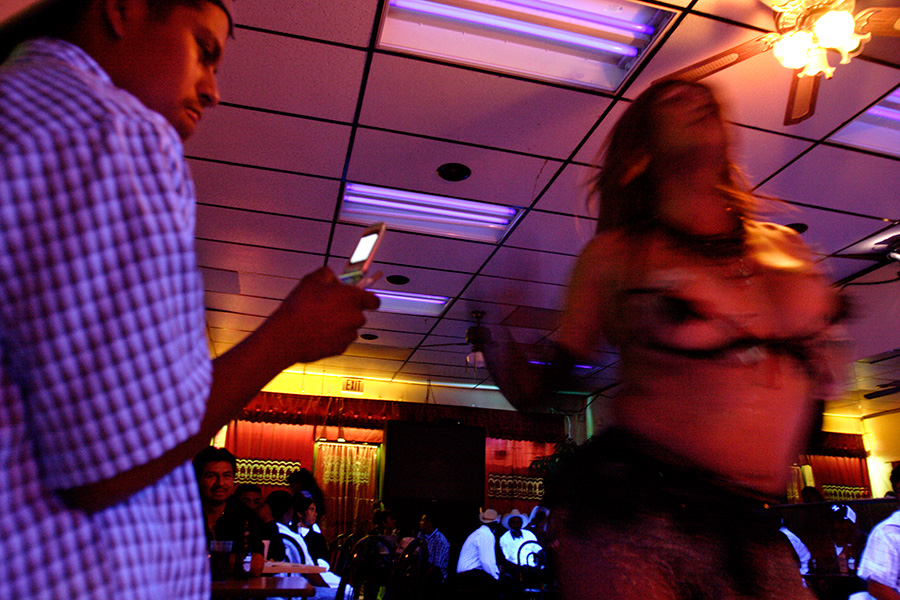 While Claudia performs her show at a local Hispanic restaurant bar, a customer tries to photograph her with his cell phone camera.