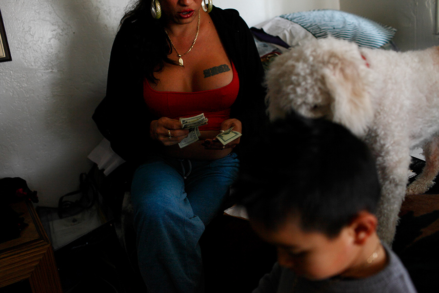 While she looks after a neighbor's young son and having her dog next to her, Claudia counts money on her bed.