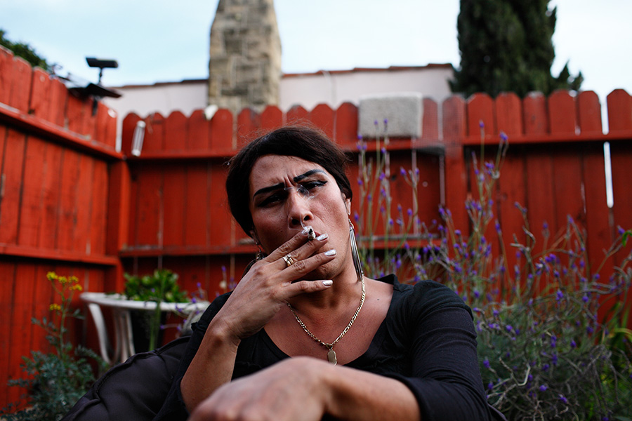Claudia smokes marijuana in the backyard.