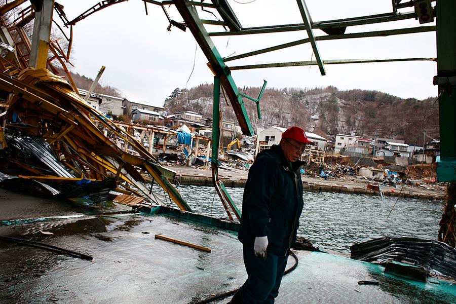 A local fisherman walks through the destructed Kuji Fish market along the Kuji Bay in Kuji, Iwate Prefecture.
