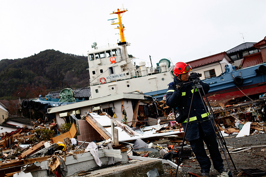 With a boat washed ashore in the background, a member of the Chinese rescue team records video footage at Ofunato, Iwate.
