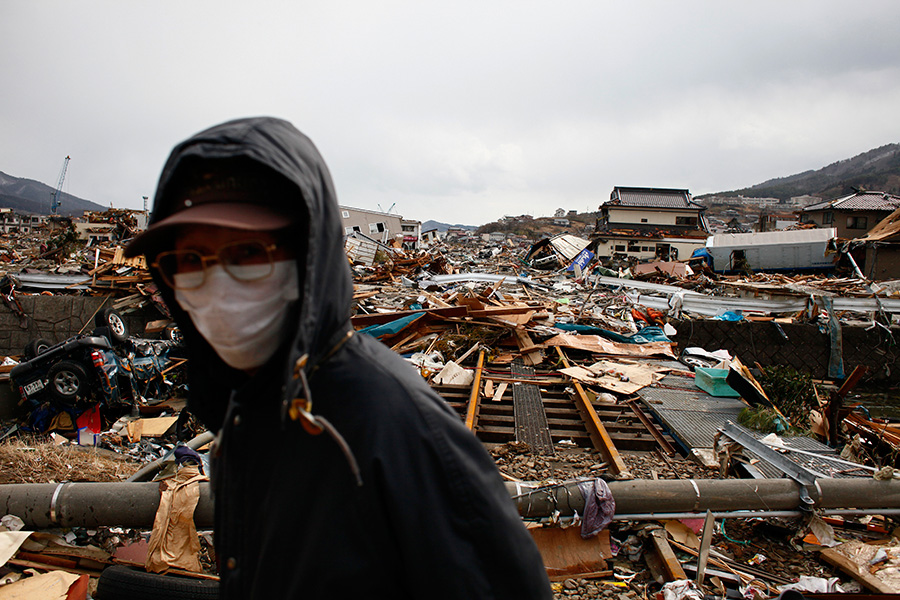 A local resident walks across debris and the railroad tracks at Ofunato, Iwate.
