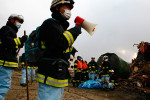 Japanese firefighters along with other search team members recover a body amongst the wreckage in Rikuzentakata, Iwate.