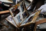 A local resident finds a family album belonging to his neighbor's under the debris where his house used to stand in Ofunato, Iwate.
