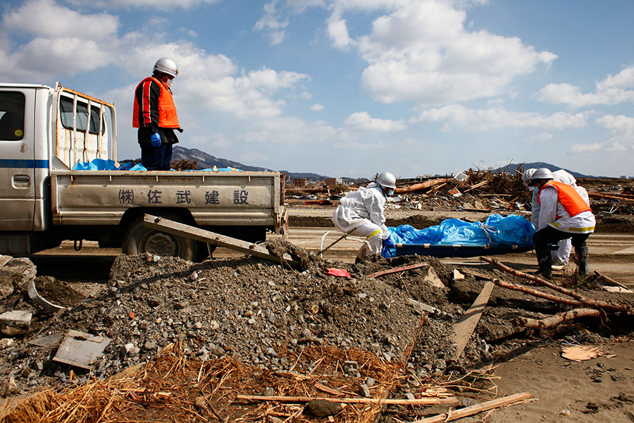 Search and rescue team locates a body and carries it away on a truck in Rikuzentakata, Iwate, Japan.