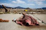 A body covered in blanket lies by a river, overlooking the city as it waits to be carried away in Rikuzentakata, Iwate Japan.
