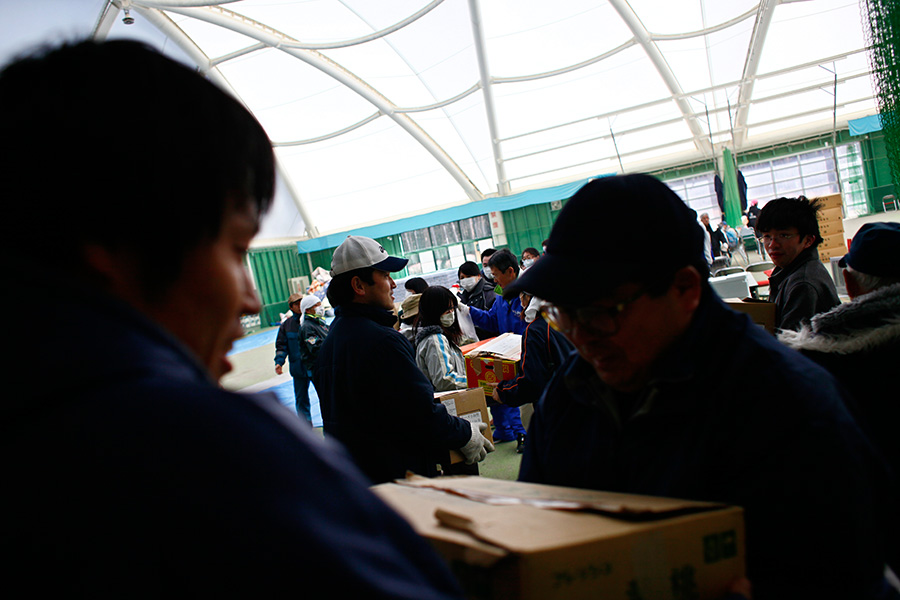 Evacuees line up to receive donated good at a shelter, originally an indoor sports facility, in Rikuzentakata, Iwate, Japan.