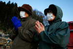 Women pray for the two found bodies in front of them amongst the rubbles in Rikuzentakata, Iwate, Japan.