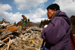 Family members try to locate their belongings where they believe their house once stood in Rikuzentakata, Iwate, Japan.
