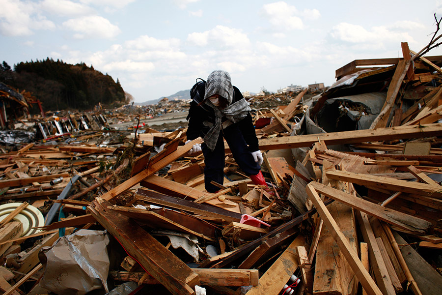 A woman tries to locate something belonging to a friend who is unaccounted for, for rememberance, amongst the rubbles in Rikuzentakata, Iwate, Japan.