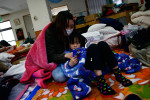 A mother and daughter read a book at a shelter in Rikuzentakata, Iwate, Japan.