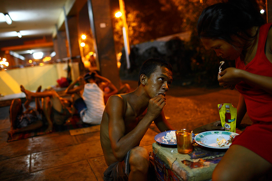 Mark 19, and his wife Mariana 19 eat dinner at the underpass entrance structure of the bus terminals.