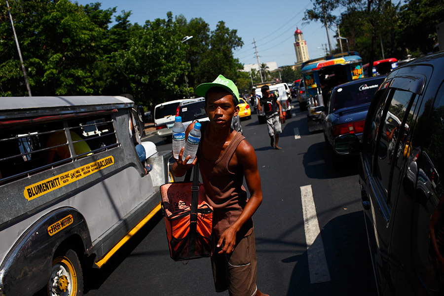 Mark walks the busy streets and sells water bottles under the scorching sun.  He buys 60 bottles at a time, 5peso per bottle and sells for 10.  Mark says business is good when traffic is busy and hot, but that makes it difficult for him as well.  He sold 60 bottles this day.