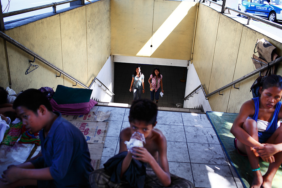 """People use the underpass structure at the bus terminal and cross """"into"""" the homeless persons' living quarters."""