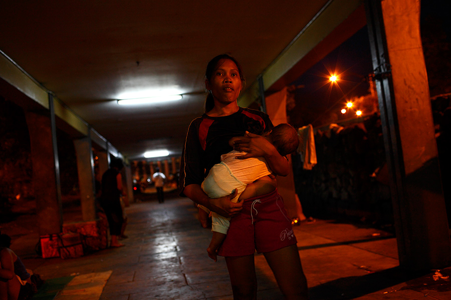 Mariana holds her 6-month-old daughter, Angela as the night falls at the underpass structure connecting the bus terminals.