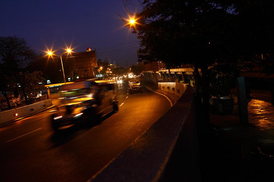 Buses roar and pass by the underpass structure of the bus terminals at night.