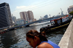 Veronica and others visit the Pasig river near where they live.  High-rise condominiums and office buildings line up along the river.