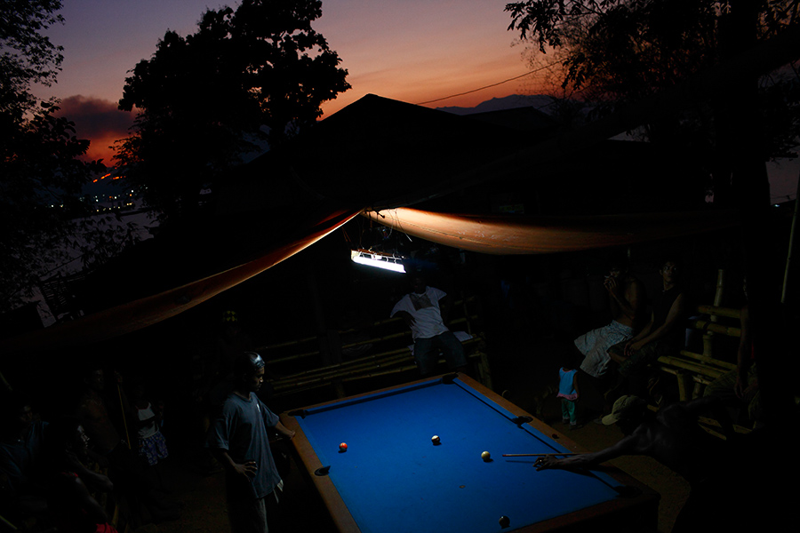 Villagers of a shanty town gather and shoot pool on an outdoor table as the sun sets in Olongapo, Philippines.