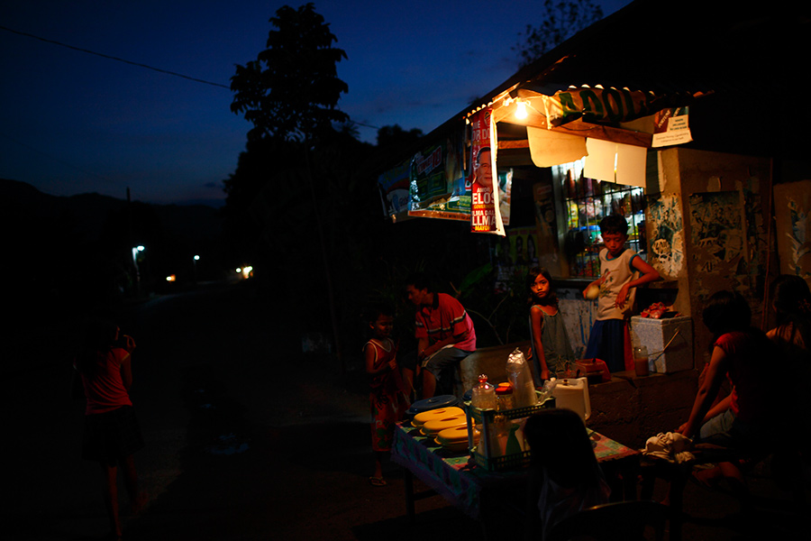 Locals gather at a small roadside market in a rural village in Castillejos, Philippines in the late evening.