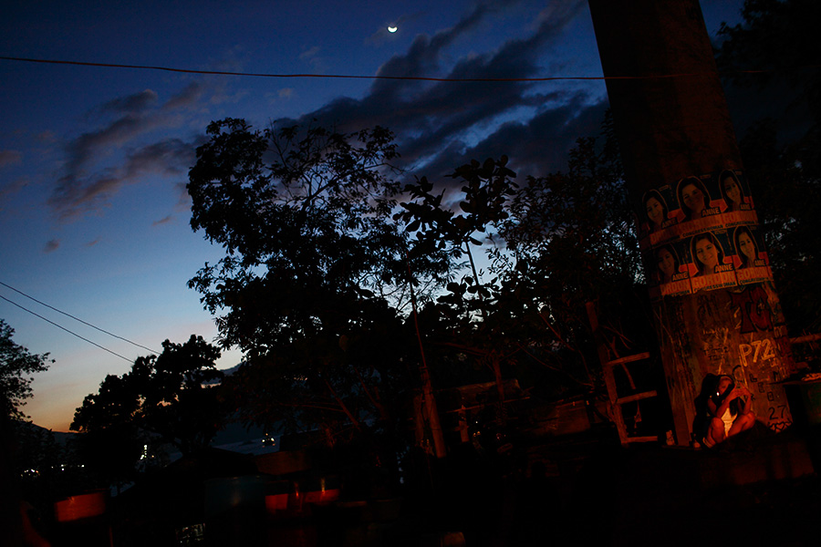 A woman uses text message on her cell phone while being lit by passing car headlights in Olongapo, Philippines.