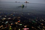 A man paddles a boat through garbage out to the shore in Baseco shanty town in Manila, Philippines.