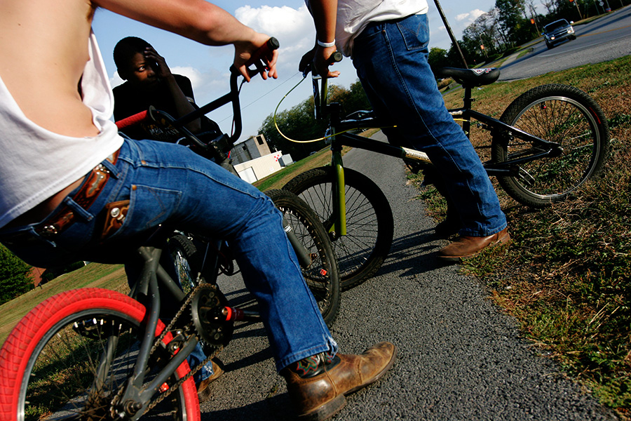 DeMarcus Macon, center, hangs out on the sidewalk near Millennium Park entrance with his bike friends with cowboy boots in Danville, KY.