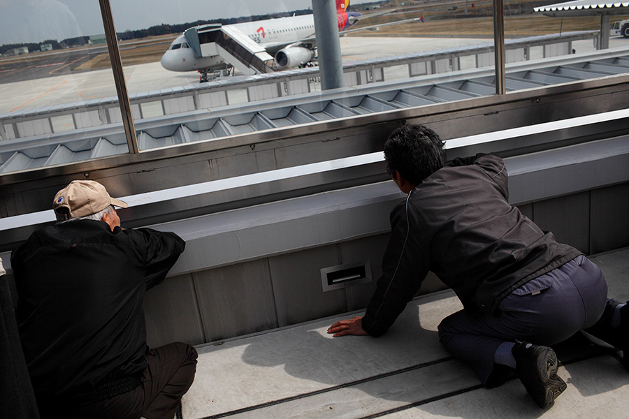 Sightseers visit the observation deck at the newly opened Ibaraki Airport outside Tokyo, Japan.  Some try to get a peek of the aircraft and the airfield from a small gap, without having to see through the protective material.  The airport currently has one scheduled flight per day going to Seoul, Korea.  Ibaraki Airport is the third airport in the Tokyo area, and aims to work with low-cost carriers primarily.