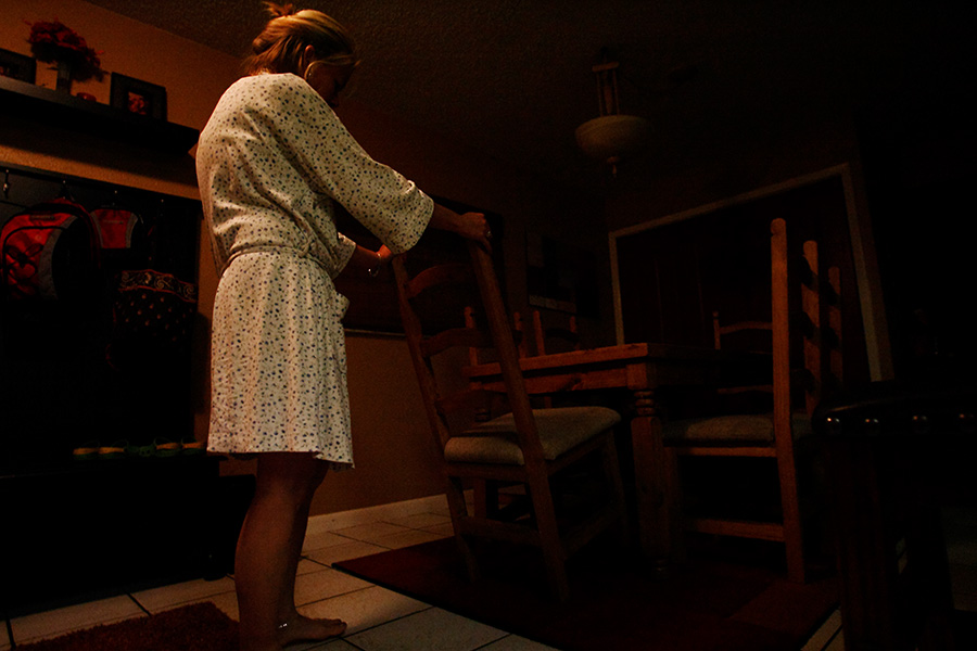 Janet stands in the dining area in the dark.  Her husband died couple years ago and has left Janet and the children with emotional and financial difficulties.