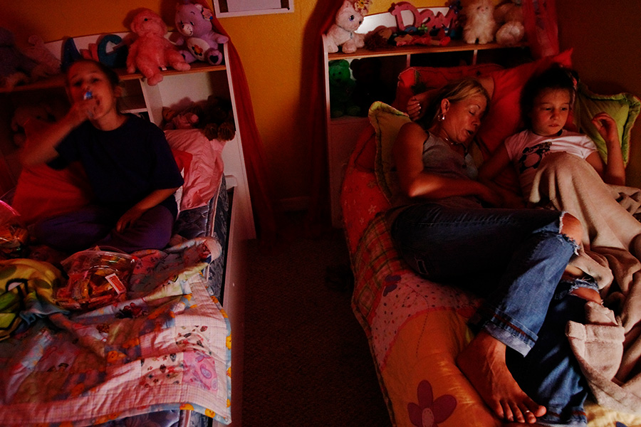 After another long day of taking care of her children, Janet tries to get some rest in the early evening by lying in bed with her autistic daughter, Nikki, while her typical child, Alex, sits on the other bed eating Halloween candies.  Although just nine-years-old, Alex is often taking care of herself and helping out Janet in watching over her autistic triplet brother and sister.