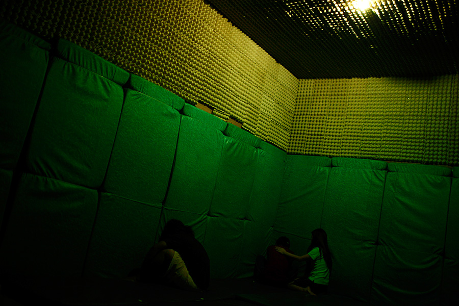 Inside a dark room lit by a single light bulb with calming music playing in the background, sexually abused and commercially sexually exploited girls release their emotions during primal therapy session.  Many cry and scream while some punch the padded walls while a therapist comforts them at local NGO in Olongapo, Philippines.