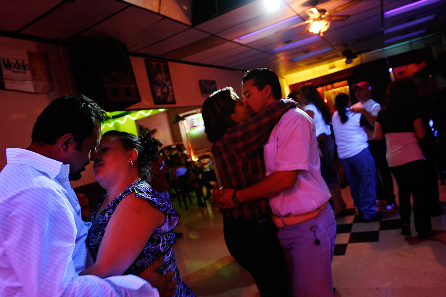 Couples kiss as they dance to the music at a Hispanic restaurant bar.