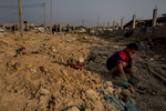 A boy plays in a construction site beside a migrant worker camp.