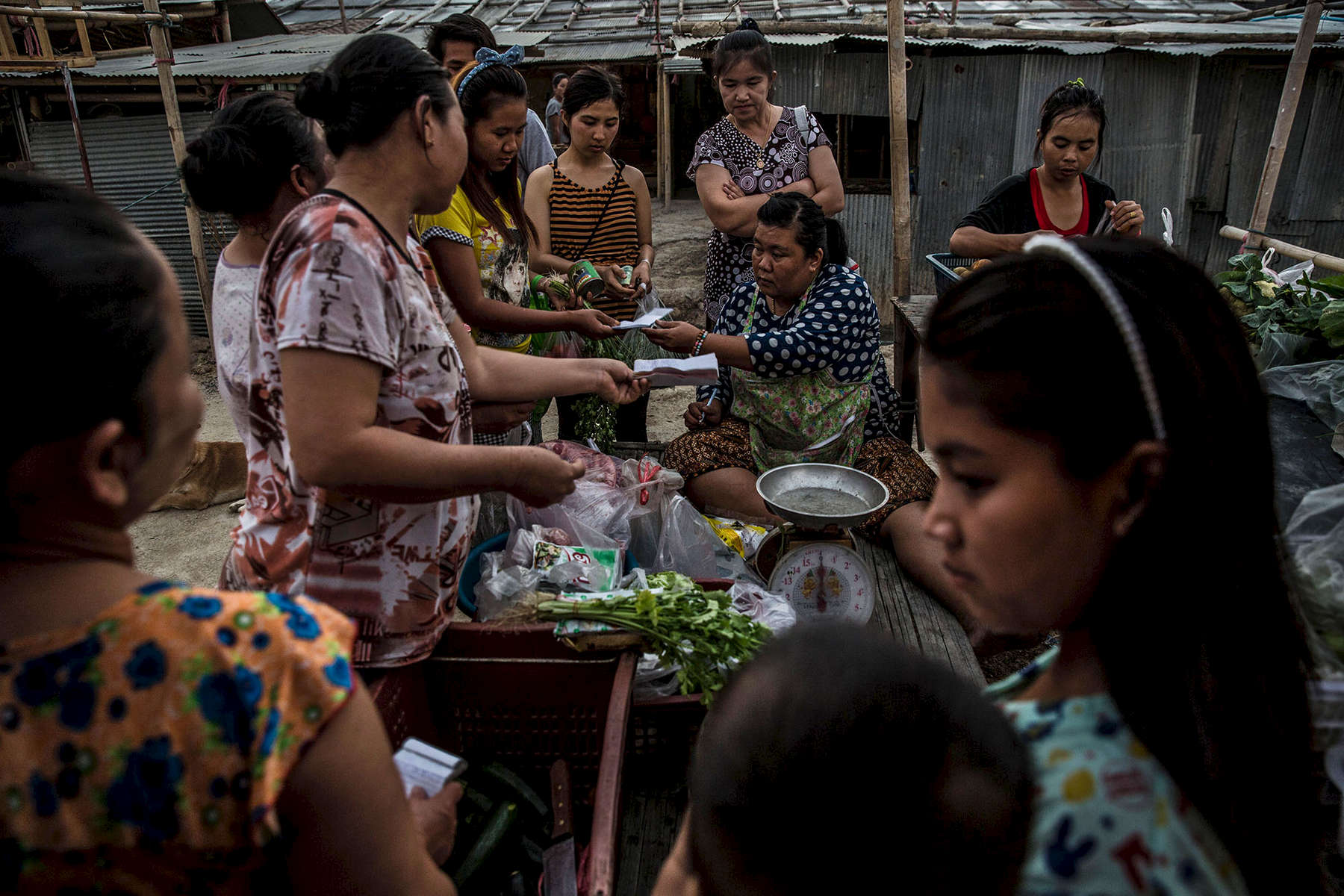 Women purchase produce from a mobile vendor that services migrant worker camps.