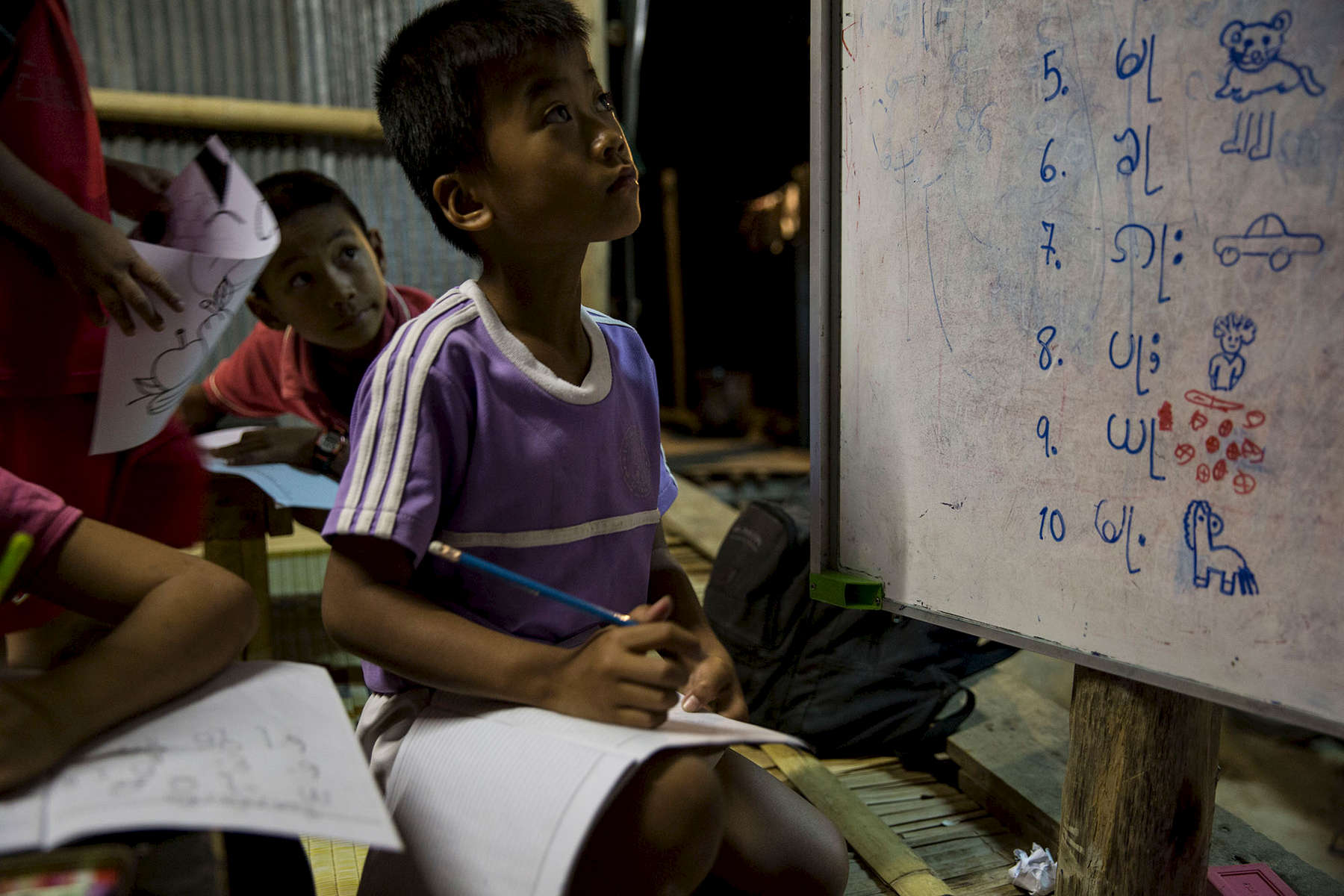 Many of the Shan children born in Thailand are at risk of losing their traditional customs and language. Here, Shan children study their native language in a makeshift night school run by NGO volunteers.
